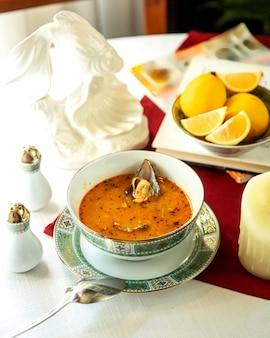 Sopa de ostras picantes com limão fatiado lateral