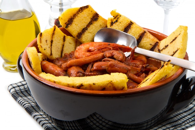 Sopa de peixe com polenta grelhada na panela de barro
