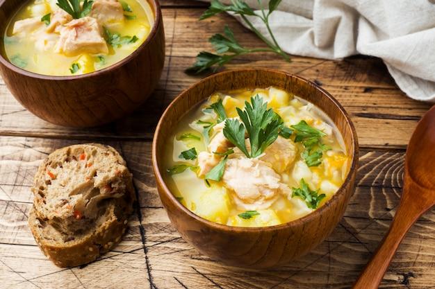 Sopa de peixe em uma tigela de madeira com ervas frescas.