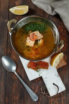 Sopa de peixe fresco com ingredientes e temperos para cozinhar. fundo de madeira