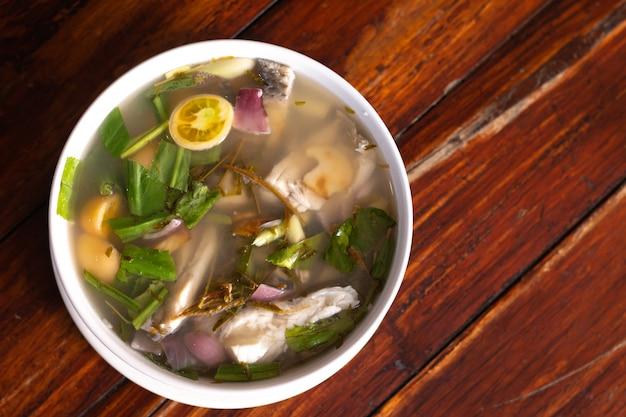 Sopa de peixe picante aromatizado com erva-cidreira e limão servido na mesa de madeira