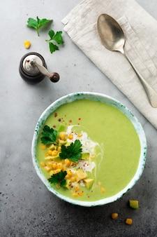 Sopa de purê caseiro de abacate e milho com creme em prato de cerâmica rústica em superfície velha de concreto cinza
