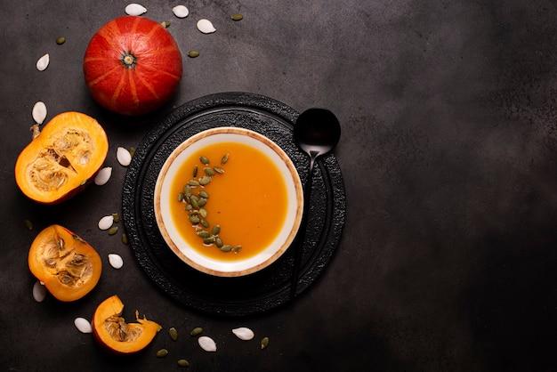 Sopa de purê de abóbora com sementes e sementes de gergelim em uma placa de luz em um quadro negro, vista de cima