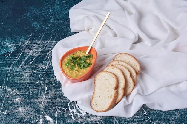 Sopa de purê de batata com ervas e fatias de pão.