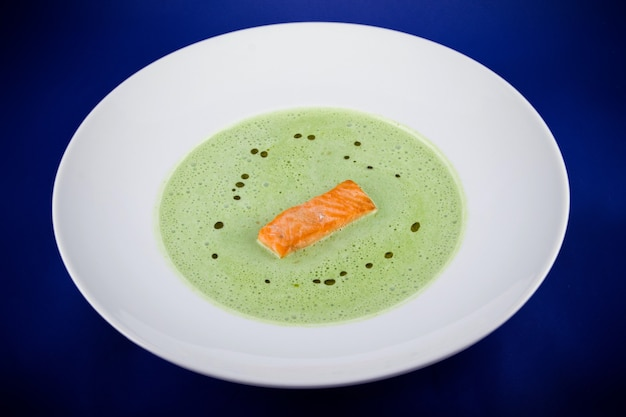 Sopa de purê de espinafre verde com rodelas de salmão. vista superior plana leiga em uma placa branca sobre um fundo azul.