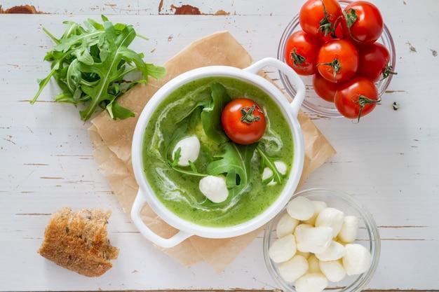 Sopa de purê de rúcula e tomate em tigela branca