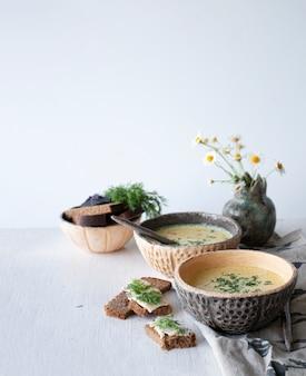 Sopa de queijo com cogumelos e legumes, pão integral com manteiga, endro e manjericão, sobre um fundo branco de madeira