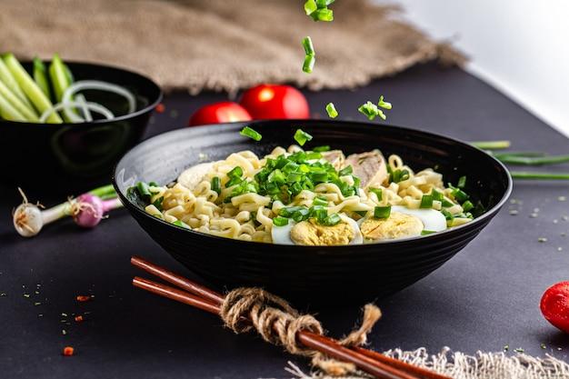 Sopa de ramen asiática com frango, ovo, cebolinha na tigela preta