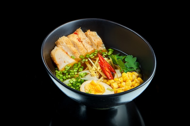 Sopa de ramen asiática tradicional com cebola, ovo, carne de porco, milho, salsa e pimenta em uma tigela preta sobre uma superfície preta com reflexão