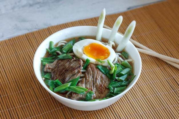 Sopa de ramen com cebola fresca, ovo cozido e carne frita