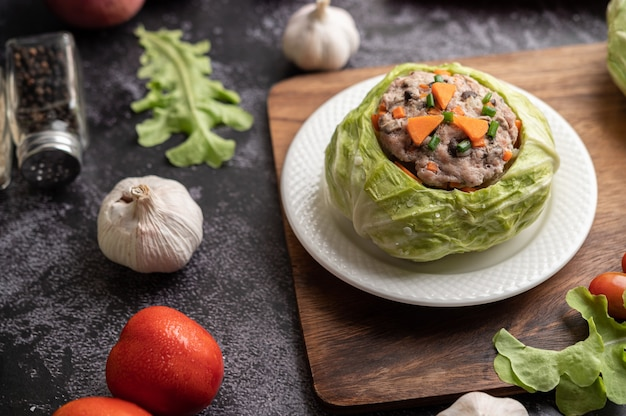 Sopa de repolho de porco com cenoura, cebolinha picada, pepino em uma placa de madeira em uma placa de madeira