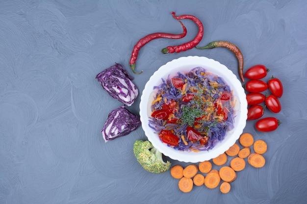 Sopa de repolho e pimenta com ingredientes na superfície azul