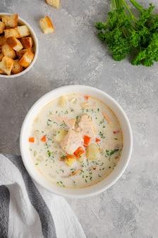 Sopa de salmão com creme, batata, cenoura, erva e croutons em uma tigela no fundo de concreto