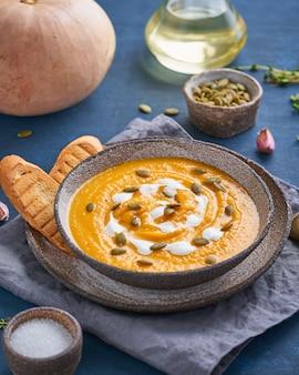 Sopa de sopa de creme pupmkin na mesa de madeira azul escura, almoço vegetariano dietético