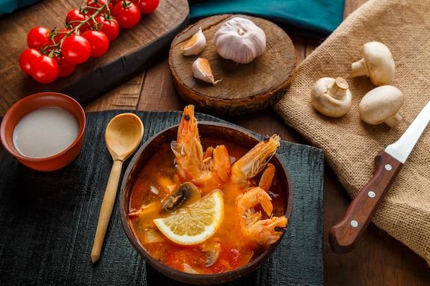 Sopa de tom inhame com camarão e leite de coco em uma mesa em um quadro negro perto de ingredientes e uma colher. foto horizontal