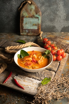 Sopa de tom yam com camarão, lula e pimenta na placa de madeira texturizada.