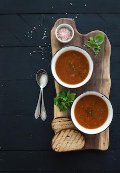 Sopa de tomate assado com manjericão fresco, especiarias e pão na tigela de metal vintage na placa de madeira sobre fundo preto