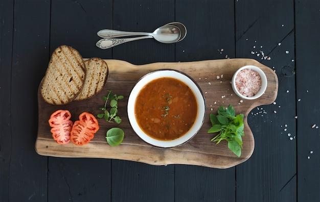 Sopa de tomate assado com manjericão fresco, especiarias e pão na tigela de metal vintage na placa de madeira