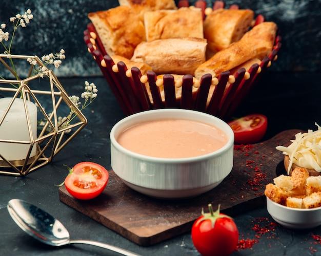 Sopa de tomate com biscoitos em boliche branco.