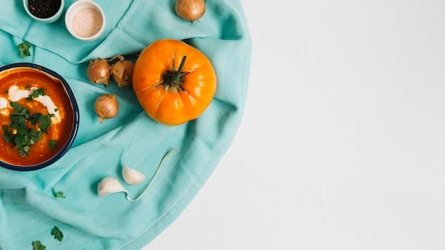 Sopa de tomate com ingredientes na superfície branca