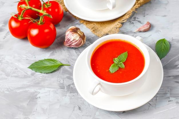Sopa de tomate com manjericão em uma tigela.
