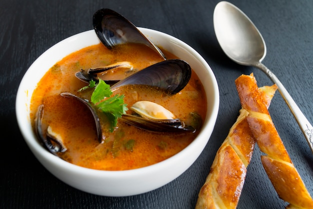 Sopa de tomate com mexilhões. com pão torrado frito em um fundo preto.