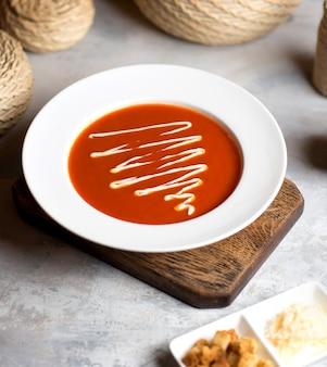 Sopa de tomate com molho na mesa