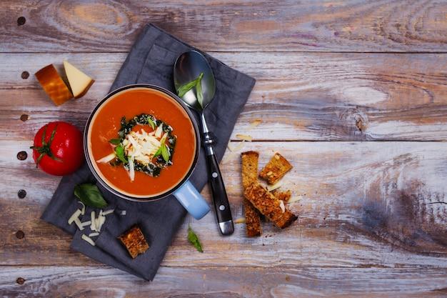 Sopa de tomate com molho pesto e queijo parmesão em um copo de cerâmica