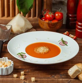 Sopa de tomate com queijo em cima da mesa