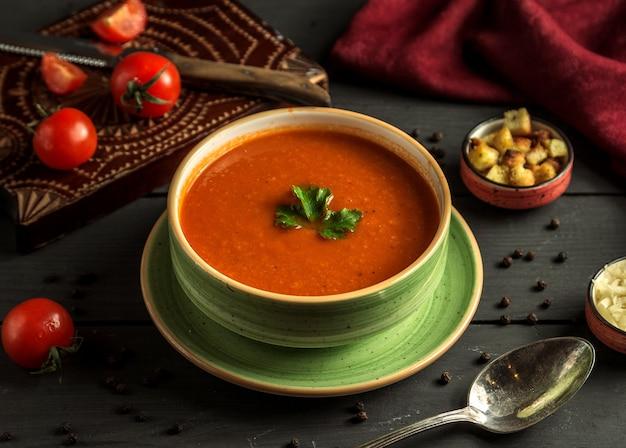 Sopa de tomate com verde em cima da mesa