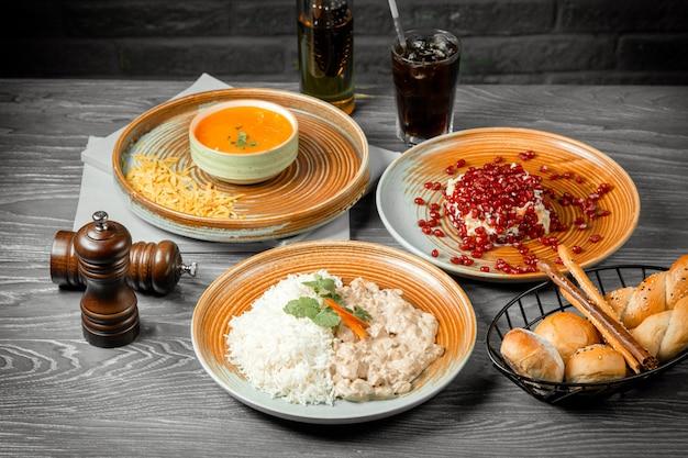 Sopa de tomate de almoço de negócios com strogonoff de frango com queijo com salada de romã de arroz, bebida de pão e pimenta preta na mesa