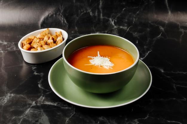 Sopa de tomate dentro da tigela verde com queijo branco picado nele com a tigela de biscoito ao redor.