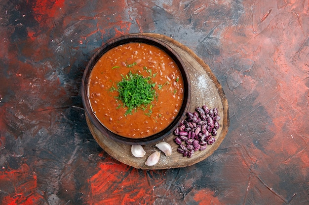 Sopa de tomate e feijão com alho em uma tábua de madeira na mesa de mistura de cores