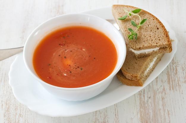 Sopa de tomate em tigela branca com sanduíche na superfície branca