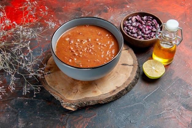 Sopa de tomate em uma tigela azul em uma bandeja de madeira marrom e garrafa de óleo de feijão na mesa de cores diferentes