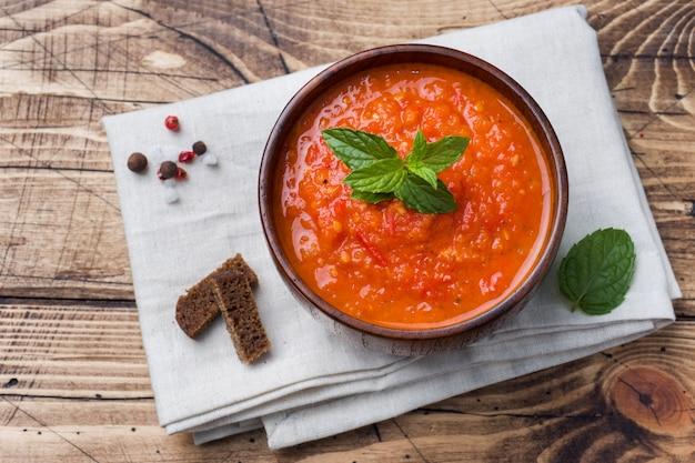 Sopa de tomate em uma tigela de madeira com pedaços de torrada em uma mesa rústica.
