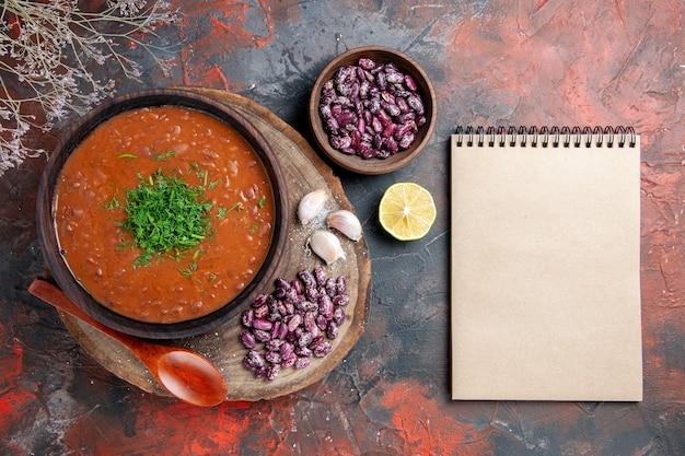 Sopa de tomate, feijão, alho na tábua de madeira, colher e caderno na mesa de cores diferentes