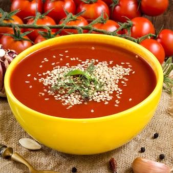 Sopa de tomate fresco com legumes e colher em uma mesa de madeira