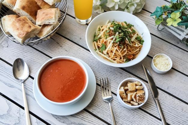 Sopa de tomate vista superior com migalhas de pão de queijo e pão na mesa