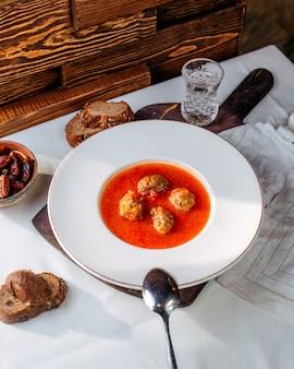 Sopa de tomate vista superior com rolos de carne dentro, juntamente com fatias de pão na mesa branca