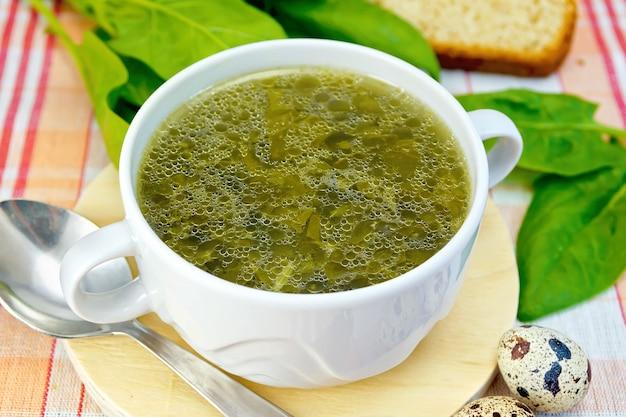 Sopa de urtiga verde, azeda, espinafre, folhas de ruibarbo em uma tábua redonda de madeira