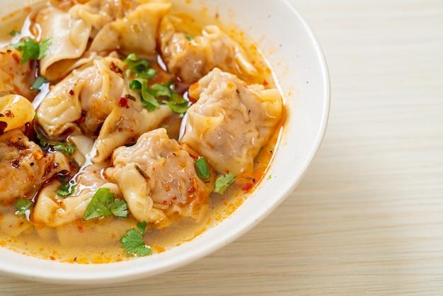 Sopa de wonton de porco ou sopa de bolinhos de porco com chili assado - comida asiática