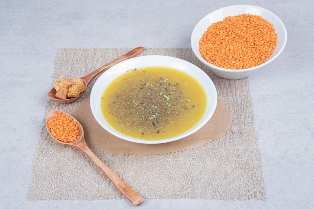 Sopa deliciosa com lentilha e colher na toalha de mesa