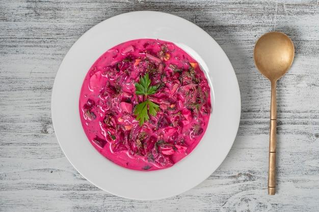 Sopa deliciosa de beterraba fria de verão com pepino, ovo cozido, rabanete em prato branco na mesa, close-up, vista de cima