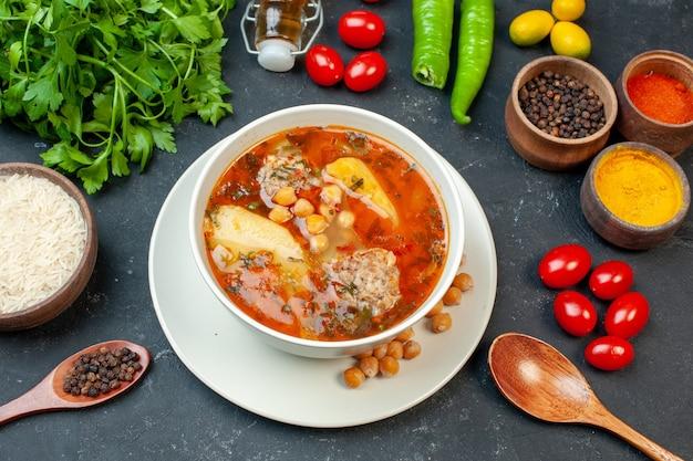 Sopa deliciosa de carne com verduras e temperos na mesa escura de frente