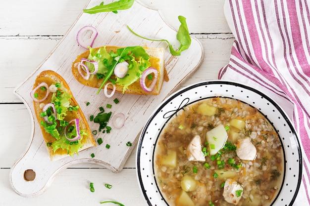 Sopa do trigo mourisco com galinha em uma placa, pão com cebola vermelha do ang da mostarda em uma tabela branca de madeira. vista do topo