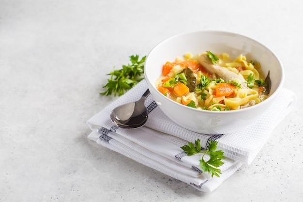 Sopa e vegetais de macarronete da galinha em uma bacia branca em um fundo branco, espaço da cópia.