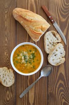 Sopa em um prato com fatias de pão sobre uma mesa de madeira. o conceito de nutrição orgânica adequada.