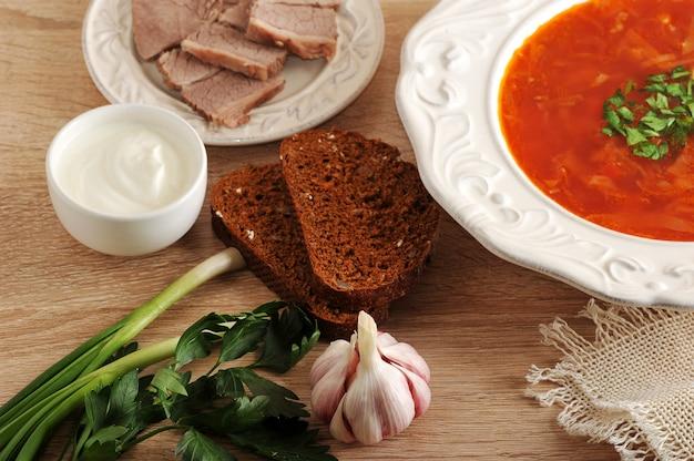 Sopa em uma tigela com endro, creme de leite, carne e pão preto na superfície de madeira