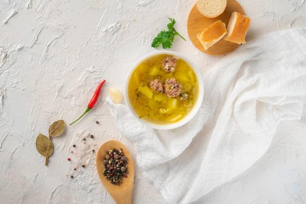 Sopa fervida fresca quente com almôndegas e batata com pão em uma mesa branca, jantares saborosos
